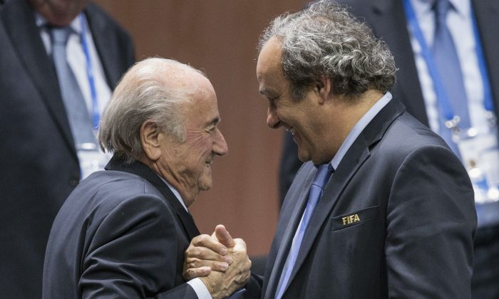 FIFA President Sepp Blatter (L) is greeted by UEFA President Michel Platini (R) after Blatters re-election as president at the Hallenstadion in Zurich, Switzerland, on May 29, 2015. (Patrick B. Kraemer/Keystone via AP)