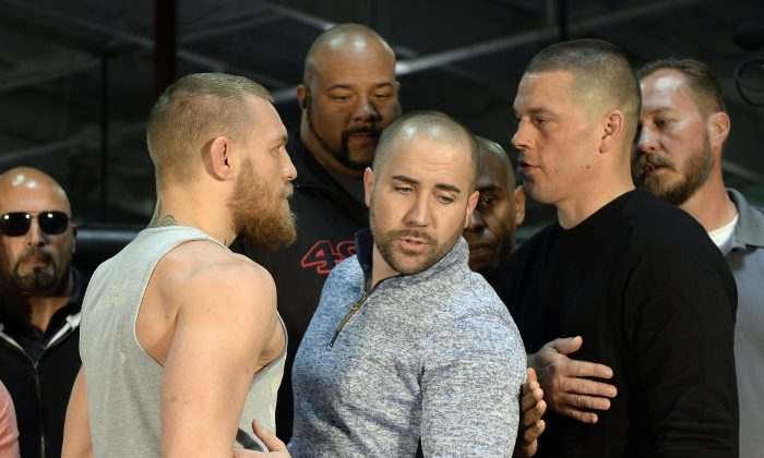 UFC featherweight champion Conor McGregor (L) and lightweight contender Nate Diaz (R) are held apart ahead of their welterweight match. (Kevork Djansezian/Getty Images)