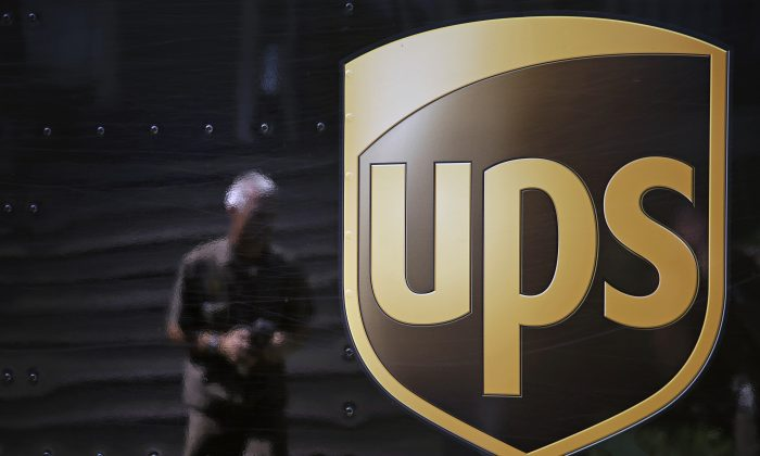 The United Parcel Service logo is seen on the side of a truck as driver Marty Thompson is reflected returning from a delivery in Cumming, Ga., on June 20, 2014. (AP Photo/David Goldman)