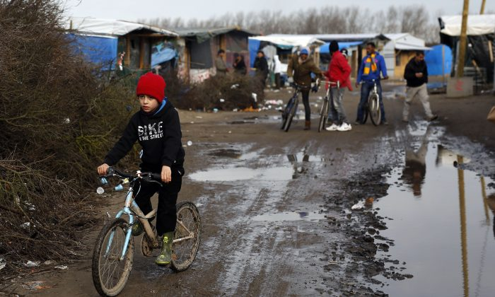"A child rides his bicycle in a makeshift camp for migrants near Calais, France, Thursday Feb. 25, 2016. The clock is ticking for some hundreds of migrants waiting for a judge to decide whether to postpone an eviction order in the camp locally referred to as ""the jungle"". (AP Photo/Jerome Delay)"