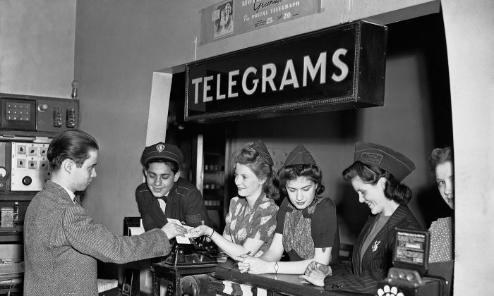 A delivery clerk gives messages for delivery to staff at the Postal Telegraph-Cable Company's Radio City office in New York in 1942.  (AP Photo/Bob Wands)