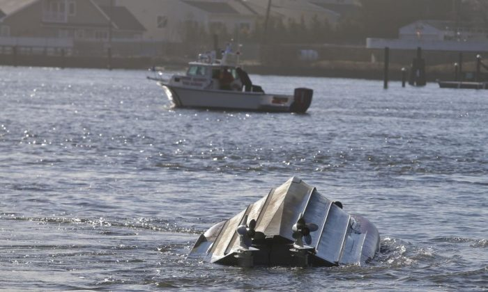 A Fire Rescue vessel passes a Coast Guard vessel that has overturned Thursday, Feb. 25, 2016, in the Queens borough of New York. Authorities say the Coast Guard vessel overturned while assisting a fishing boat that ran aground in an inlet off New York City. (AP Photo/Frank Franklin II)