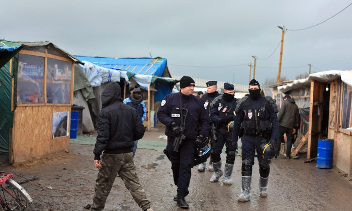 French riot police officers patrol in the migrant camp in Calais, north of France, Friday, Feb. 5, 2016. (AP Photo/Thibault Camus)