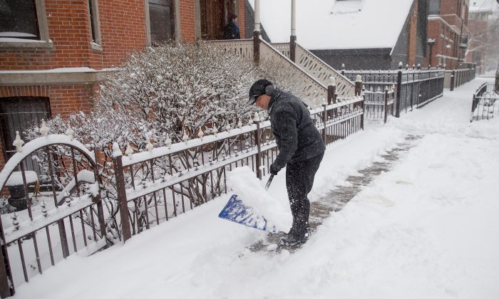 Mike Brisson clears snow from the sidewalk in front of his home as a spring storm passes through the area on March 23, 2015 in Chicago, Illinois. (Scott Olson/Getty Images)