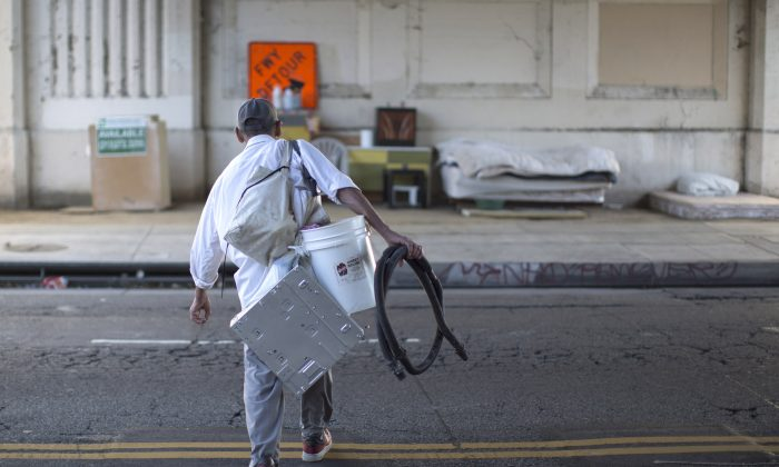 Fernando Lopez carries possessions to his street side encampment which is protected from minor storms by an overpass on November 20, 2015 in Los Angeles, California. (David McNew/Getty Images)