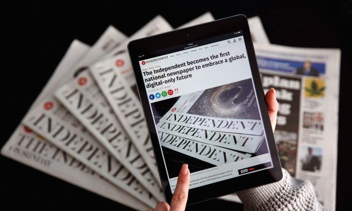 An iPad displays the Independent's online platform above a selection of the print versions of their titles on Feb. 12, 2016. (Dan Kitwood/Getty Images)