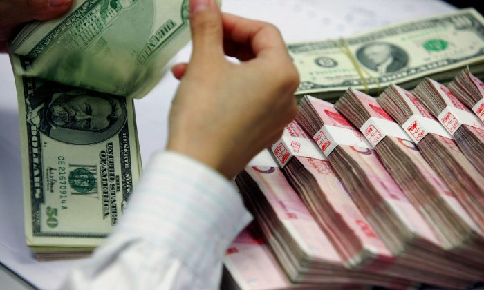 A bank teller counts the stack of Chinese yuan and US dollars at a bank in Shanghai, 22 July 2005. (STR/AFP/Getty Images)