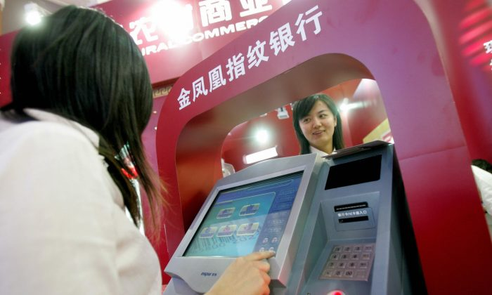 Chinese promoters show off the latest automated-teller machines at banking exhibition in Beijing 13 September 2007.  (STR/AFP/Getty Images)