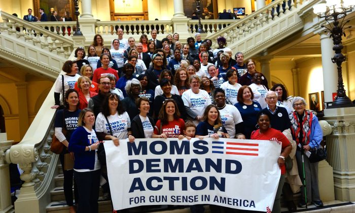 "Moms Demand Action, who advocate for what they call ""gun sense,"" pose on the steps of the Georgia Capitol in Atlanta on Feb. 24, 2016. Advocates, lobbyists, and students packed the building to talk to their representatives during the legislative session. (Mary Silver/Epoch Times)"