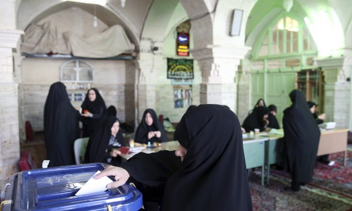 An Iranian woman votes in the parliamentary and Experts Assembly elections at a polling station in Qom, 125 kilometers (78 miles) south of the capital Tehran, Iran, Friday, Feb. 26, 2016. (AP Photo/Ebrahim Noroozi)