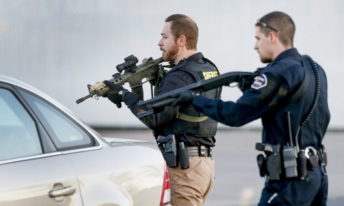 Police look for a possible second shooter in the parking lot of  Excel Industries in Hesston, Kan., Thursday, Feb. 25, 2016, where a gunman killed an undetermined number of people and injured many more. (Fernando Salazar/The Wichita Eagle via AP)
