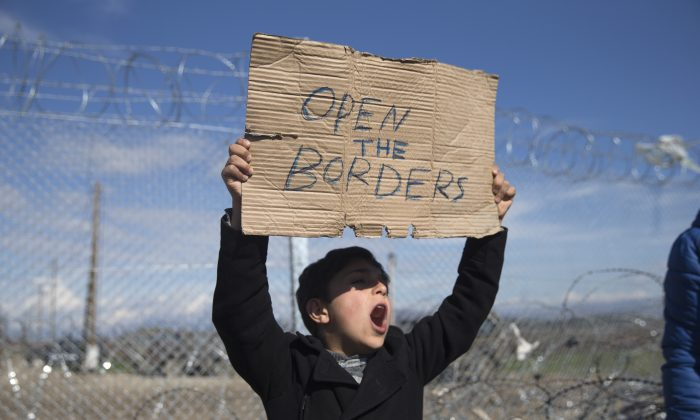 A boy shouts slogans as he holds a placard during a protest by refugees and migrants in front of the wire fence that separates the Greek side from the Macedonian one at the northern Greek border station of Idomeni on Feb. 27, 2016. (AP Photo/Petros Giannakouris)