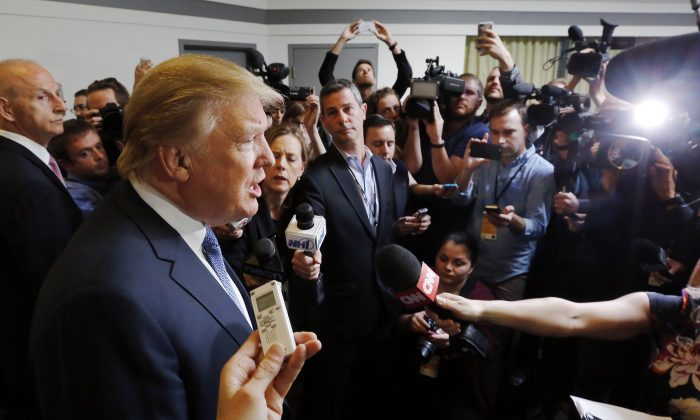 Republican presidential candidate Donald Trump talks to reporter before speaking at a No Labels Problem Solver convention Monday, Oct. 12, 2015, in Manchester, N.H. (AP Photo/Jim Cole)