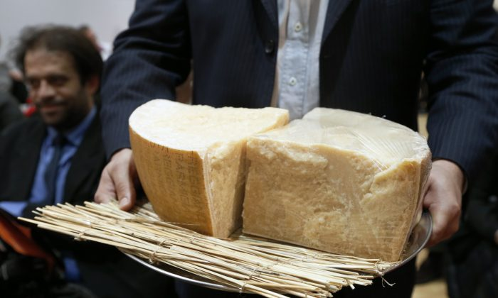 A man presents pieces of parmesan during a sale of fine food to raise funds for the French Red Cross on December 18, 2012 French auction house Artcurial in Paris. AFP PHOTO FRANCOIS GUILLOT (FRANCOIS GUILLOT/AFP/Getty Images)