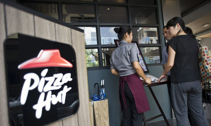 A staff member attends to customers browsing the menu of Pizza Hut's first restaurant in Yangon on October 22, 2015. (Ye Aung Thu/AFP/Getty Images)