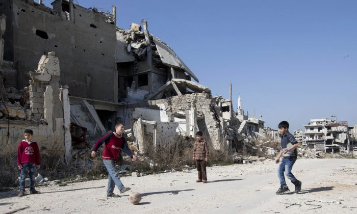 Syrian boys play soccer between destroyed buildings in the old city of Homs, Syria, on Feb. 26, 2016. (AP Photo/Hassan Ammar)