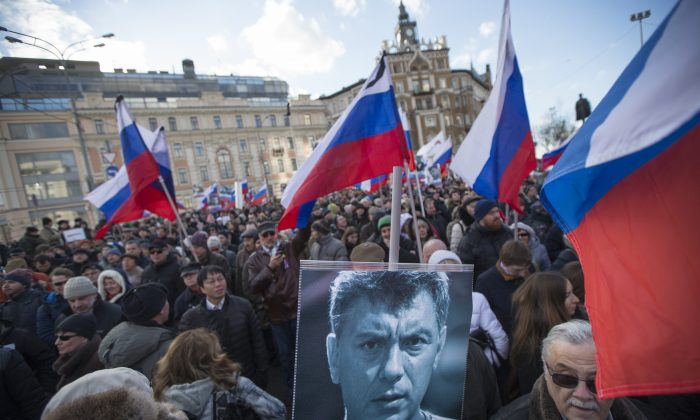 Demonstrators hold a portrait of slain opposition leader Boris Nemtsov and Russian flags during a march marking the one-year anniversary of his killing, in Moscow, Russia, on Feb. 27, 2016. Several thousand people took part in the march. (AP Photo/Ivan Sekretarev)