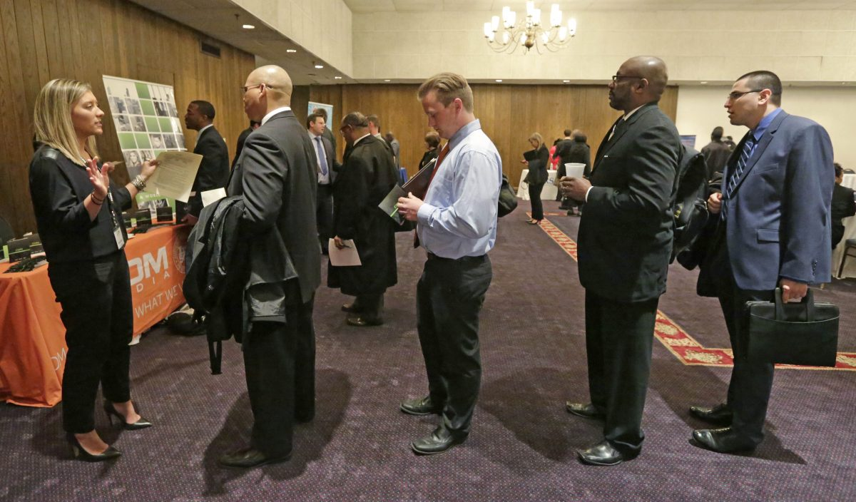 Bianca Medici (L), a corporate recruiter for CDM Media, speaks with job applicants during a National Career Fairs job fair in Chicago on April 22, 2015. The Labor Department releases weekly jobless claims on May 14, 2015. (AP Photo/M. Spencer Green)