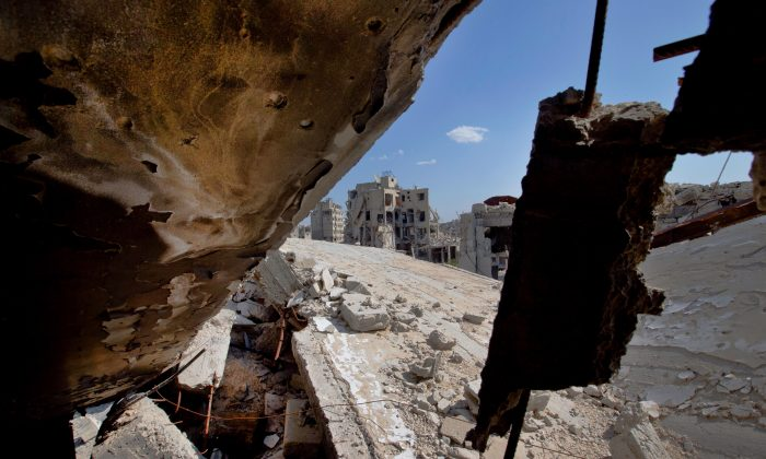 "Destroyed buildings are seen in the old city of Homs, Syria, on Feb. 26, 2016. Some 1,200 rebels and civilians, many of them wounded and starving from a yearlong siege, withdrew from the last remaining strongholds in the ancient heart of Homs in May 2014, surrendering to President Bashar Assad, a bloodstained city once dubbed the ""capital of the revolution."" (AP Photo/Hassan Ammar)"
