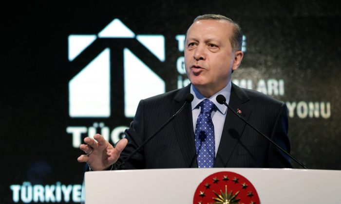 """Turkish President Recep Tayyip Erdogan addresses a meeting in Ankara, Turkey, on Feb. 11, 2016. Erdogan has confirmed the minutes of a leaked conversation between himself and top European Union officials last year in which he threatens to send buses full of migrants to Europe if a favorable deal on handling the crisis is not reached. Erdogan said Thursday the minutes showed that he had defended the rights of Turkey and of the Syrians, adding it was not """"a document of shame."""" (Murat Cetinmuhurdar/Presidential Press Service via AP)"""