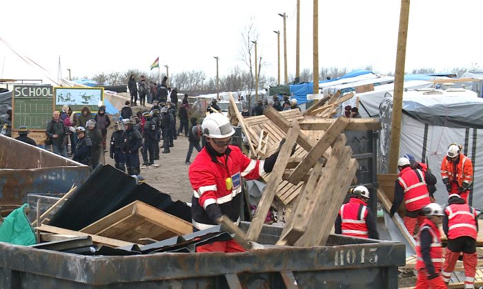 Police officers safeguard helmeted workers pulling down makeshift structures where migrants sleep in the southern sector of the camp near the northern port of Calais, France, Monday, Feb. 29, 2016. French authorities have begun dismantling the sprawling migrant camp in Calais where thousands are hanging out, hoping to make their way to a better life in Britain. (AP Photo/Chris den Hond)