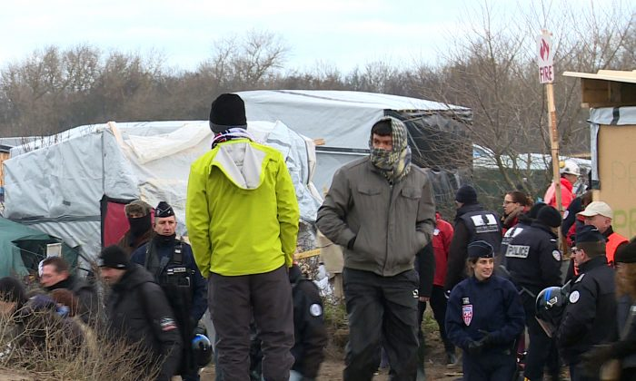 Migrants watch police officers taking positions in the southern sector of the camp near Calais, northern France, Monday, Feb. 29, 2016. French authorities have begun dismantling the sprawling migrant camp in Calais where thousands are hanging out, hoping to make their way to a better life in Britain. (AP Photo/Chris den Hond)