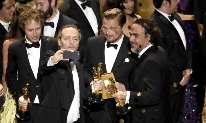 Emmanuel Lubezki, from left, Leonardo DiCaprio, and Alejandro G. Inarritu take a selfie on stage at the conclusion of the show at the Oscars, Feb. 28, 2016, at the Dolby Theatre in Los Angeles. (Chris Pizzello/Invision/AP)