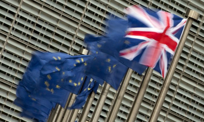A Friday, Jan. 29, 2016 photo from files showing the British, right, and EU flags flapping in the wind outside of EU headquarters in Brussels. (AP Photo/Virginia Mayo)
