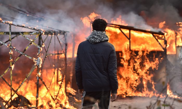 """A migrant looks at shacks burning during the dismantling of half of the """"Jungle"""" migrant camp in the French northern port city of Calais, on February 29, 2016. Clashes broke out between French riot police and migrants on February 29 as bulldozers moved into the grim shantytown on the edge of Calais known as the """"Jungle"""" to start destroying hundreds of makeshift shelters. AFP PHOTO / PHILIPPE HUGUEN / AFP / PHILIPPE HUGUEN        (Photo credit should read PHILIPPE HUGUEN/AFP/Getty Images)"""