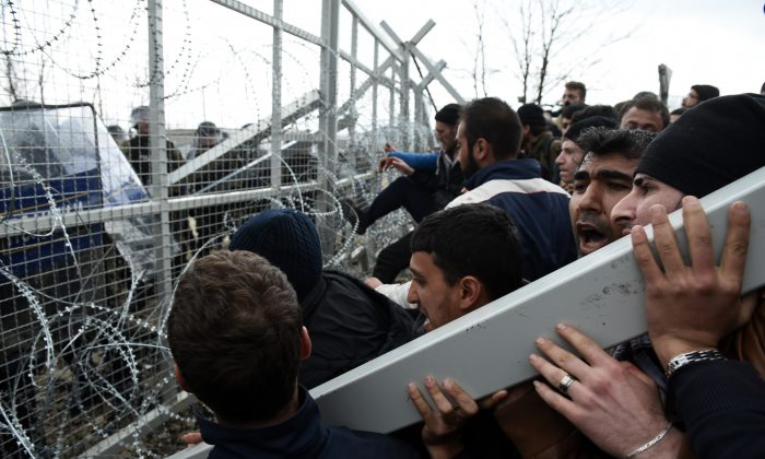 Refugees and migrants try to break an iron fence from the Greek side of the border as Macedonian police stand guard, near the northern Greek village of Idomeni on Feb. 29, 2016. (AP Photo/Giannis Papanikos)