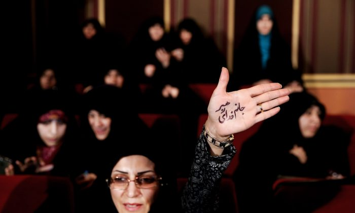 "An Iranian hard-liner raises her palm with Persian that reads, ""I'm ready to sacrifice myself for the Supreme Leader,"" during an anti-British campaign aimed at claiming reformist rivals of being backed by the BBC and the British government, in Tehran, Iran, on Feb. 24, 2016. Iranian moderates won a 59 percent majority in the Assembly of Experts, an 88-member body which will choose the successor to Ayatollah Ali Khamenei, who has been Iran's top decision-maker since 1989. The 76-year-old underwent prostate surgery in 2014, leading to renewed speculations about the state of his health. (AP Photo/Ebrahim Noroozi)"