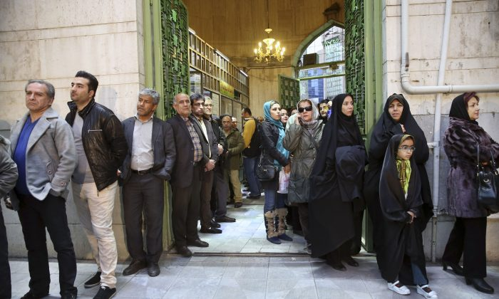 Iranians queue for voting in the parliamentary and Experts Assembly elections in a polling station in Tehran, Iran, on Feb. 26, 2016. (AP Photo/Vahid Salemi)