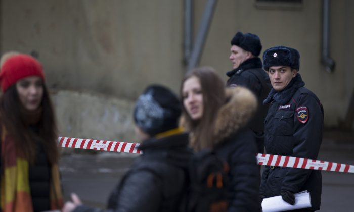 Russian police officers secure an area near to a subway station in Moscow on Monday, Feb. 29, 2016. Russian news agencies report that police have arrested a woman who was waving the severed head of a small child outside a Moscow subway station. The Investigative Committee released a statement saying a woman was arrested Monday on suspicion of killing a child aged 3 or 4 in an apartment near the metro station in northwestern Moscow and then setting the apartment on fire.  (AP Photo/Alexander Zemlianichenko)