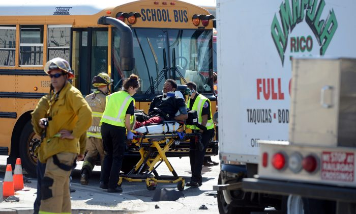 A man is transported to an ambulance at the scene of an accident involving a stolen taco truck and a school bus Monday, Feb. 29, 2016, in San Bernardino. Authorities in Southern California say two men fleeing from police in a stolen taco truck sideswiped a school bus full of children, took down the lights at an intersection and smashed into a propane truck. (Jennifer Cappuccio Maher/The Inland Valley Daily Bulletin via AP)  MANDATORY CREDIT