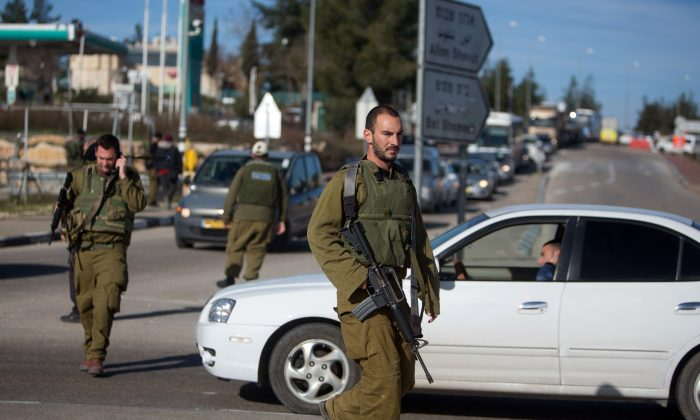 Israeli soldiers stand guard at the Gush Etzion junction in the Israeli occupied West Bank on the main road between Jerusalem and Hebron on January 5, 2016 (MENAHEM KAHANA/AFP/Getty Images)