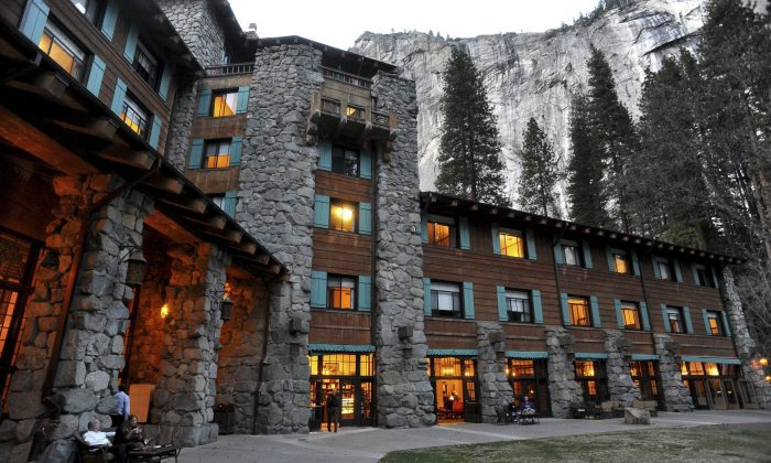The historic Ahwahnee Hotel is lit up as dusk falls over Yosemite National Park, Calif, on March 24, 2014. A new concessionaire takes over Tuesday at the park and many of the landmark places will have name changes at least temporarily because the old concessionaire lays claim to the names. The famed Ahwahnee Hotel is set to become the Majestic Yosemite Hotel. (John Walker/Fresno Bee via AP, File)
