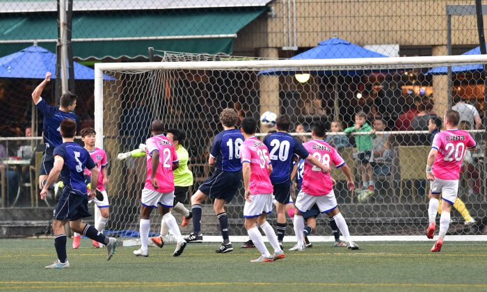 Lucky Mile (Blue) score with a fine angle header in their HKFA division 1 match at Sports Road on Sunday Feb 28, 2016, but Tai Chung were too good on the day, coming away with a 3-1 win. (Bill Cox/Epoch Times)