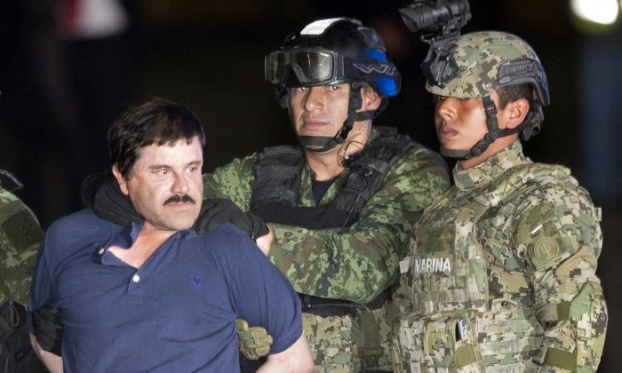 """Joaquin """"El Chapo"""" Guzman is made to face the press as he is escorted to a helicopter in handcuffs by Mexican soldiers and marines at a federal hangar in Mexico City, Mexico, on Jan. 8, 2016. (AP Photo/Eduardo Verdugo)"""