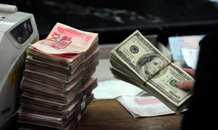A Chinese bank teller prepares to count a stack of U.S. dollars together with stacks of 100 Chinese yuan notes at a bank in Hefei, Anhui Province, China on March 9, 2010. (STR/AFP/Getty Images)