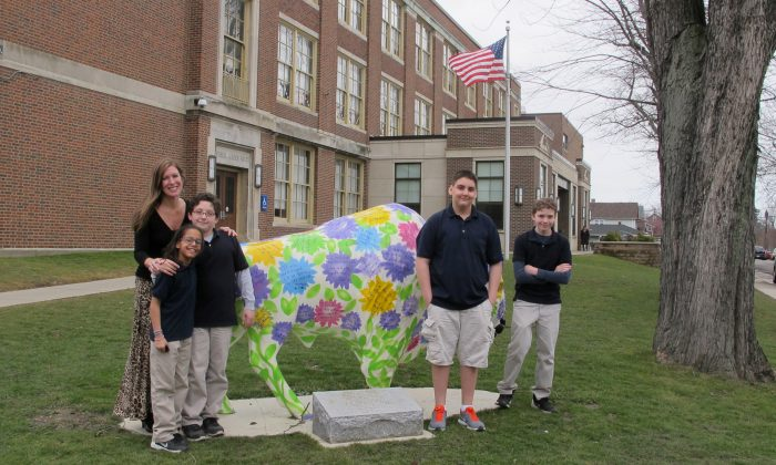 Teacher Kelly Gasior (L) and students stand with a statue of a Buffalo that's been emblazoned with anti-bullying messages outside Lorraine Academy, Public School No. 72, in Buffalo, N.Y. Educators in Buffalo and elsewhere worry the name-calling, mocking and social media attacks that have gotten applause in the presidential campaign could undermine schools' bullying prevention policies that call for kindness and respect. (AP Photo/Carolyn Thompson)