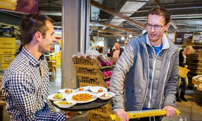 An employee offers samples of snacks made from insects to a customer in a store of Dutch supermarket chain Jumbo in Groningen (Remko de Waal/AFP/Getty Images)