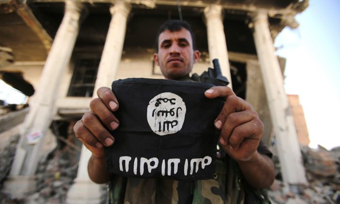 An Iraqi Shiite fighter from the Popular Mobilization units holds an ISIS patch in north of Tikrit, in the Salahaddin province, on June 7, 2015. (Ahmad Al-Rubaye/AFP/Getty Images)