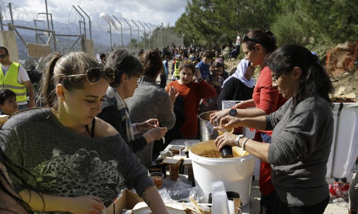 Volunteers serve food to migrants queuing outside the registration and hospitality centre, known as hotspot, of the eastern Greek Island of Samos, on the Aegean Sea,Thursday, March 3, 2016. (AP Photo/Lefteris Pitarakis)