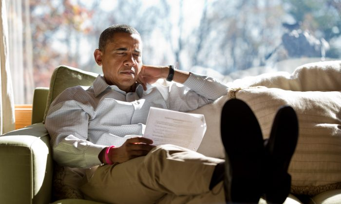 President Barack Obama reads briefing material while meeting with advisors inside his cabin at Camp David, Sunday, Oct. 21, 2012. (Official White House Photo by Pete Souza)