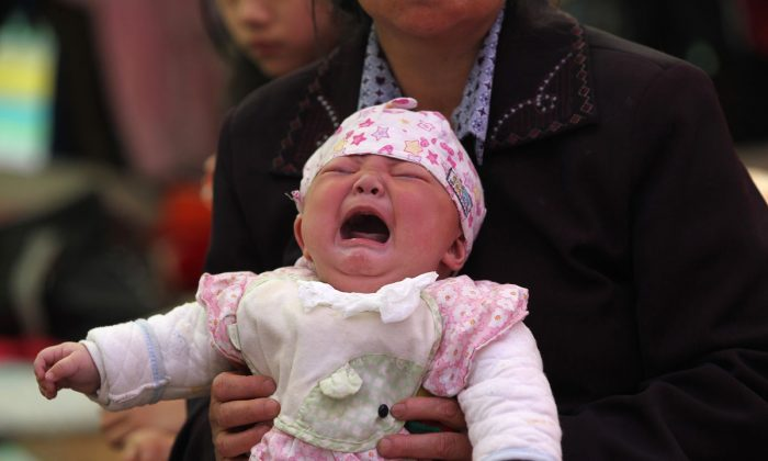 This photo taken on April 23, 2013 shows 4-month-old Li Jie crying in her mother's arms inside a temporary settlement in Lingguan township of Baoxing county in Yaan, southwest China's Sichuan province. (AFP/AFP/Getty Images)