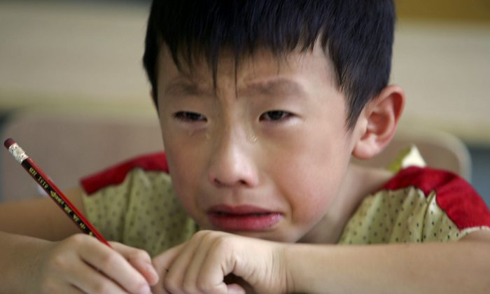 "A boy cries during class at the West Point Training Center in Zhejiang on Aug. 2, 2006. A ""tiger mom"" in China makes her son study 16 hours everyday. (Cancan Chu/Getty Images)"