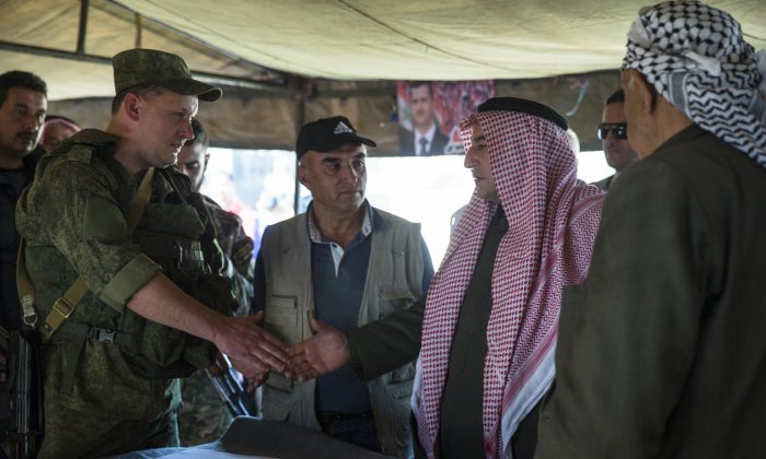 FILE -- In this March 2, 2016, file photo, Sheikh Ahmad Mubarak, second from right, shakes hands with a Russian military officer after signing a cease-fire declaration in Maarzaf, about 15 kilometers west of Hama, Syria. A shaky cease-fire in Syria brokered by Moscow and Washington has survived its first week, outlasting expectations and providing a glimmer of hope that a diplomatic solution to the five-year-old war may be possible.(AP Photo/Pavel Golovkin, File)