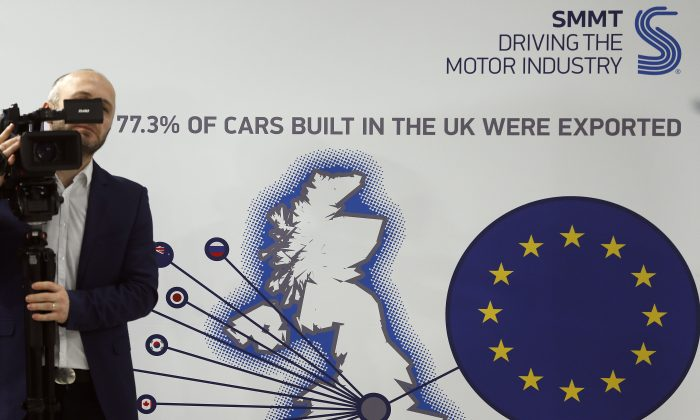 A cameraman films during a press conference of the Society of Motor Manufacturers and Traders Limited (SMMT) U.K. automotive, focusing on Europe in London, on March 3, 2016. Britain's Society of Motor Manufacturers and Traders said Thursday that 77 percent of its members backed remaining in the 28-nation bloc. Britain will hold a referendum on EU membership June 23. (AP Photo/Frank Augstein)