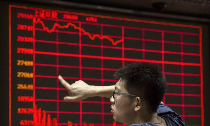 A Chinese day trader reacts as he watches a stock ticker at a local brokerage house in Beijing on Aug. 27, 2015. (Kevin Frayer/Getty Images)
