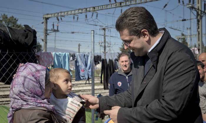 Apostolos Tzitzikostas, the regional governor of the Greek region of Central Macedonia, speaks to a migrant woman, at the northern Greek border station of Idomeni on March 5, 2016. He called on the Greek government Saturday to declare a state of emergency for the area surrounding the Idomeni border crossing saying that up to 14,000 people are trapped in Idomeni, while another 6,000-7,000 are being housed in refugee camps around the region, meaning the area was handling about 60 percent of the total number in the country. (AP Photo/Vadim Ghirda)